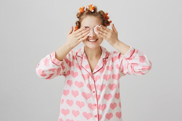 ヘアカーラーとパジャマを着て、綿のパッドで寝る前にかわいい女の子の離陸メイク