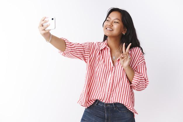 新しいスマートフォンで自分撮りをしているかわいい女の子。ストライプのブラウスで外向的で社交的な若いコミュニケーションの女性の肖像画は、電話のカメラで写真を撮って広く笑っている勝利のサインを示しています