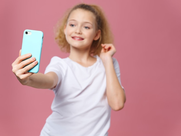 Cute girl taking selfie with smartphone