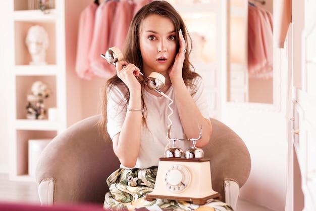 Cute girl talking on retro telephone in pink dressing room