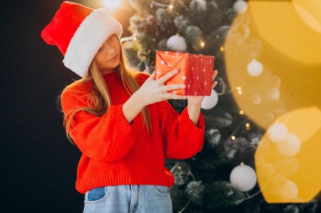 Ragazza carina adolescente in cappello rosso della santa da albero di natale
