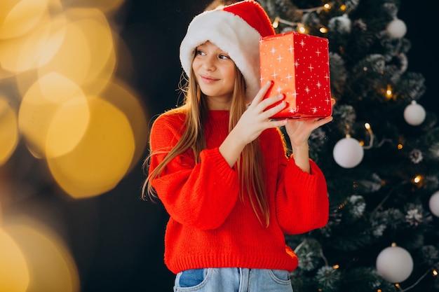 Cute girl teenager in red santa hat by christmas tree