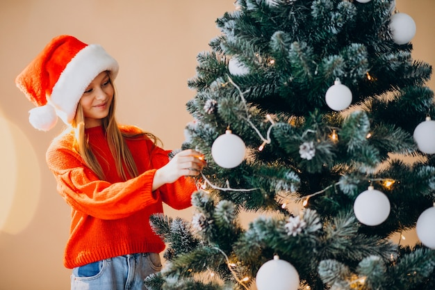 Cute girl teenager in red santa hat by christmas tree