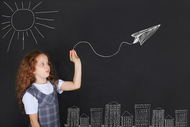 Cute girl throwing paper airplane near blackboard.