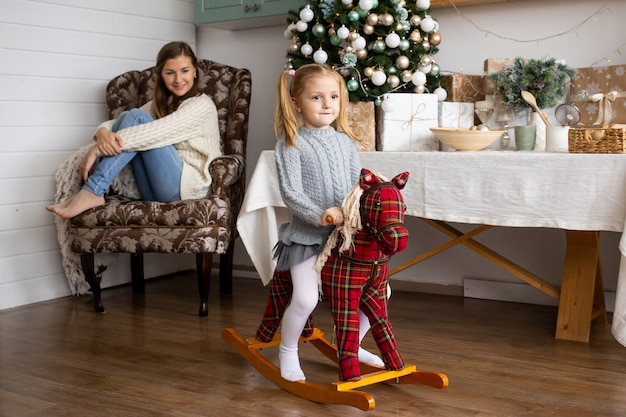 Cute girl on toy horse in christmas kitchen at home.