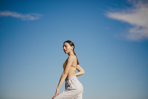 Cute girl training on blue sky
