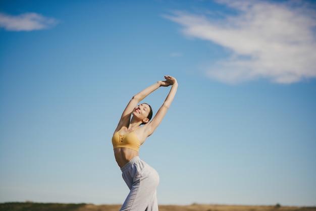 Милая девушка тренируется на голубом небе