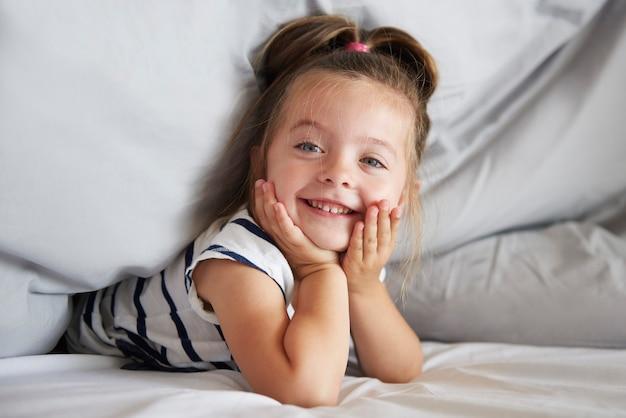 Милая девушка под одеялом