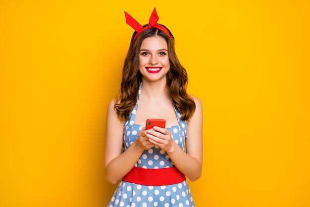 귀여운 소녀 노란색 배경 위에 스마트 폰 블로깅 게시물을 사용