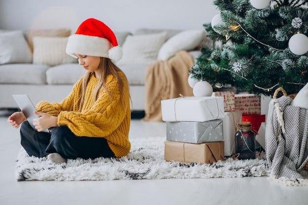 クリスマスツリーでコンピューターを使用してかわいい女の子