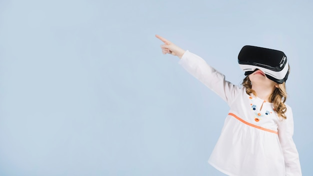 Cute girl using virtual headset pointing her finger at something