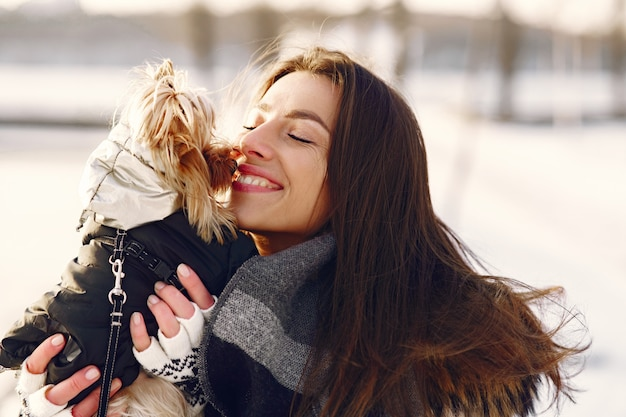 彼女の犬と一緒に冬の公園を歩いているかわいい女の子
