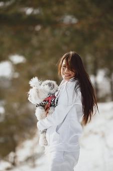 冬の公園を歩いているかわいい女の子。茶色のジャケットを着た女性。犬を連れた女性。