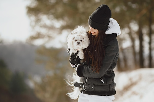 겨울 공원에서 산책하는 귀여운 소녀. 갈색 재킷에 여자입니다. 강아지와 레이디.
