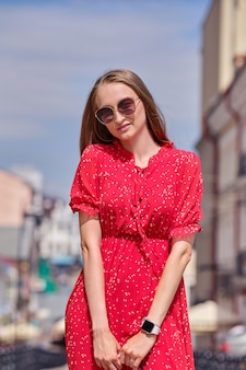 Cute girl walks in the middle of the street in sunny day