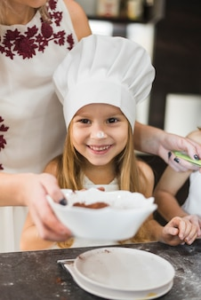 Cute girl wearing chef hat standing in front mother while cooking in kitchen