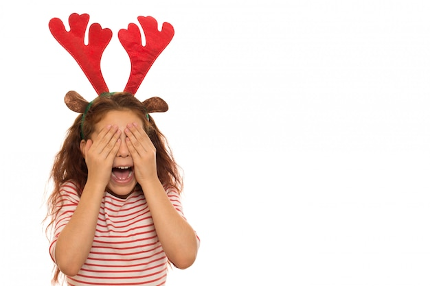 Cute girl wearing christmas antlers and crying
