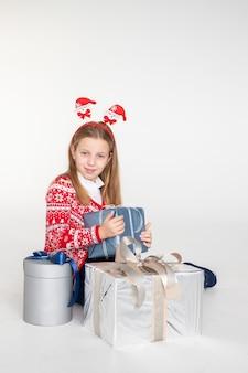 Милая девушка в рождественской повязке на голову сидит изолированно на белой поверхности