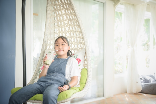 Cute girl wearing a denim overalls is drinking ice green tea and relax in white  house. leisure and relax concept