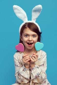 Милая девушка в ушах пасхального кролика с двумя печеньями в форме сердца