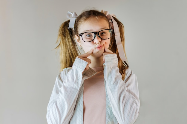 Cute girl wearing eyeglasses touching her cheeks