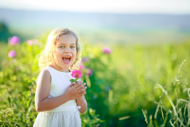 모자와 흰색 드레스를 입고 귀여운 소녀 sunn 대마 crotalaria juncea의 분홍색 꽃밭에 서