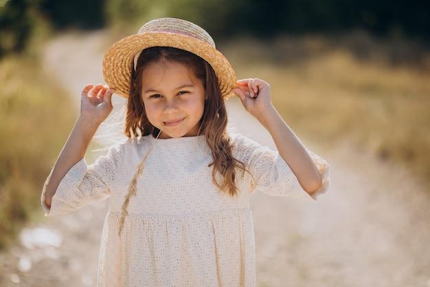 牧草地を歩いて帽子をかぶっているかわいい女の子
