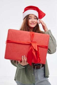 Милая девушка в шляпе санта-клауса, новогодний подарок, рождественский стиль жизни, счастье studio. фото высокого качества