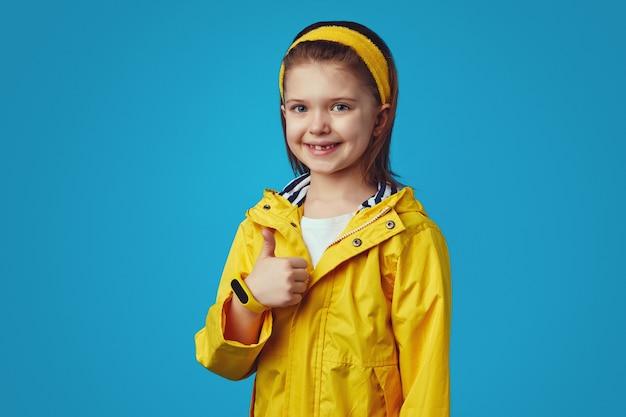 Милая девушка в желтом плаще с капюшоном имеет хорошее настроение, показывая большой палец вверх