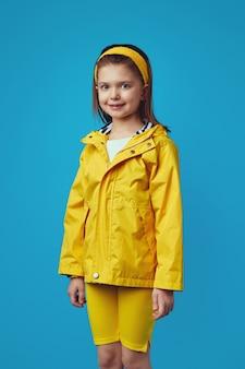 Милая девушка в желтом плаще с капюшоном над синей стеной имеет хорошее настроение