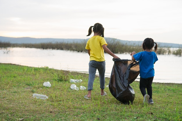 Cute girl while helping sibling to clean up garbage
