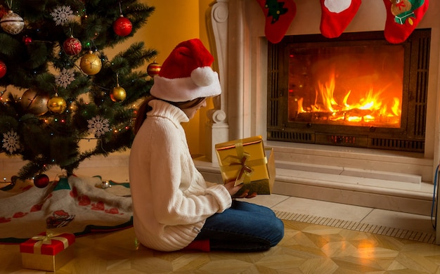 Cute girl in white sweater and santa hat sitting with christmas gift at fireplace