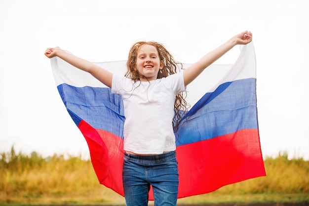 Cute girl in white t-shirt hold national russian flag.