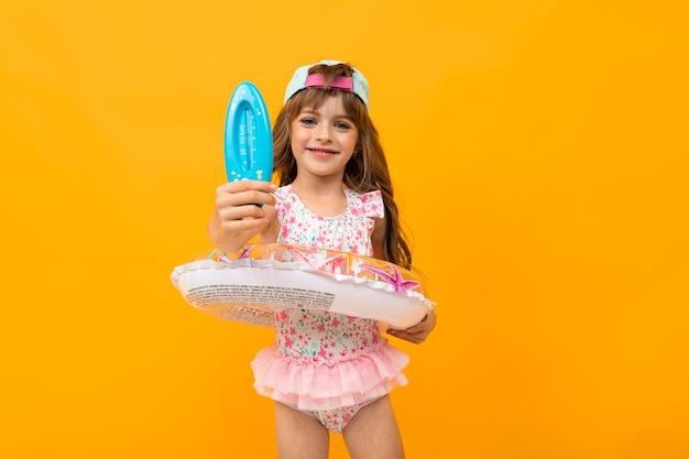 Милая девушка в бейсболке в купальнике с плавательным кругом держит термометр для воды на желтом чистом фоне.