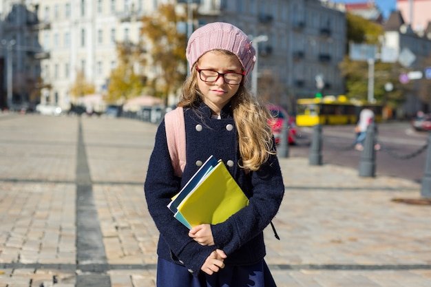 Cute girl with backpack notebooks in coat