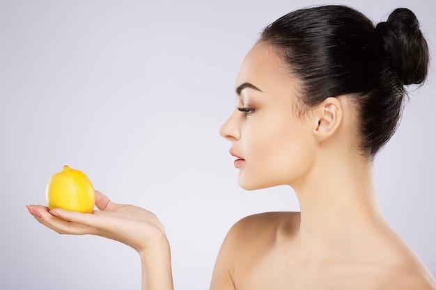 Симпатичная девушка с черными волосами, зафиксированными сзади, большими глазами, густыми бровями и обнаженными плечами у серой стены, копией пространства, портретом, держащим лимон, красоткой.