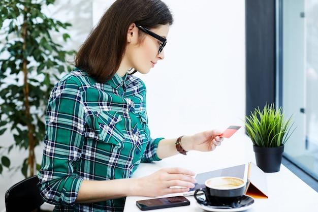 タブレットとコーヒー、フリーランスのコンセプト、クレジットカード、オンラインショッピングを持ってカフェに座っているシャツと眼鏡を身に着けている黒い髪のかわいい女の子。