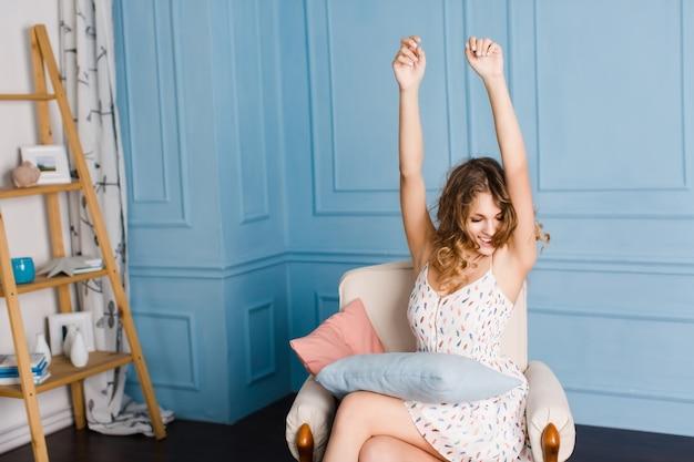 Ragazza carina con capelli ricci biondi si siede sulla poltrona in studio con pareti blu con un cuscino sulle ginocchia.