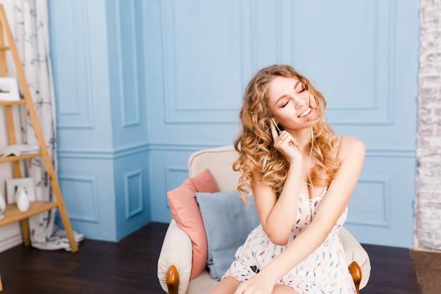 ブロンドの巻き毛のかわいい女の子は、青い壁と茶色の家具が付いているスタジオのアームチェアに座っています。