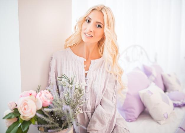 Милая девушка со светлыми волосами в фиолетовом платье и белых носках сидит на кровати в светлой спальне