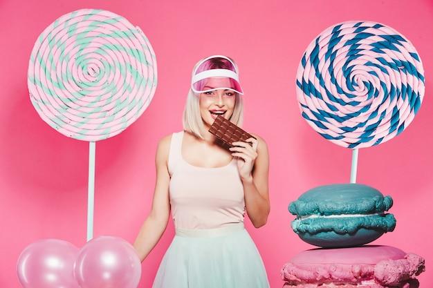 분홍색에 거대한 달콤한 막대 사탕으로 서있는 상단과 치마를 입고 금발 머리를 가진 귀여운 소녀