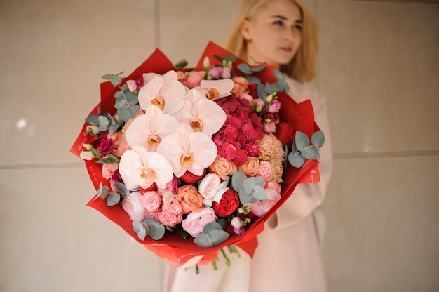 Cute girl with bouquet of roses and irises