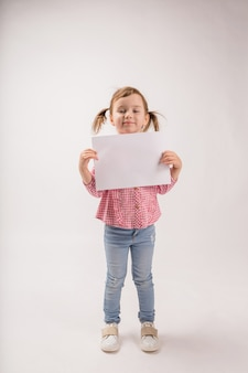 A cute girl with braids on a white space holds a white sheet with copy space. a little girl in a plaid shirt and jeans holds a leaf with an ad.