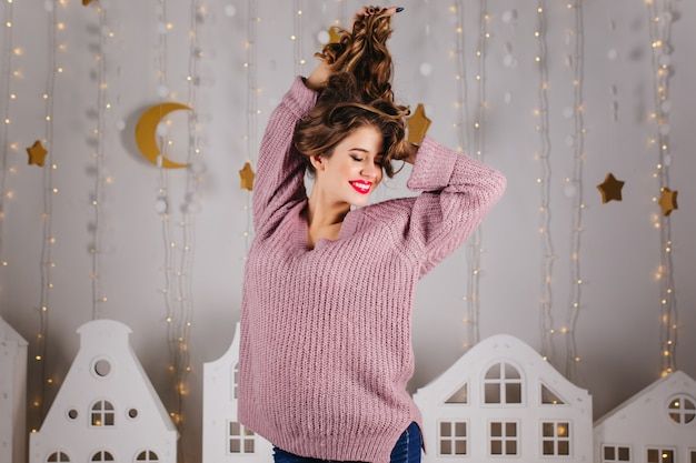 Cute girl with bright lips in purple sweater plays hair and smiles against with luminous garlands and toy houses.