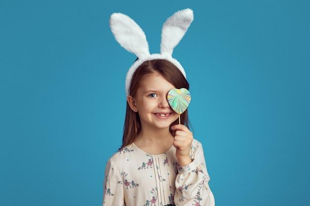 Милая девушка с кроличьими ушками прячет глаз за печеньем в форме сердца