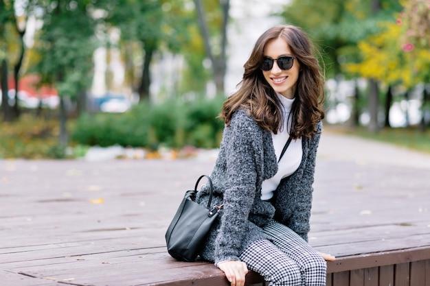 매력적인 미소와 검은 머리를 가진 귀여운 소녀는 햇빛에가 공원에서 이완합니다. 그녀는 나무 테이블에 앉아 웃고있다.