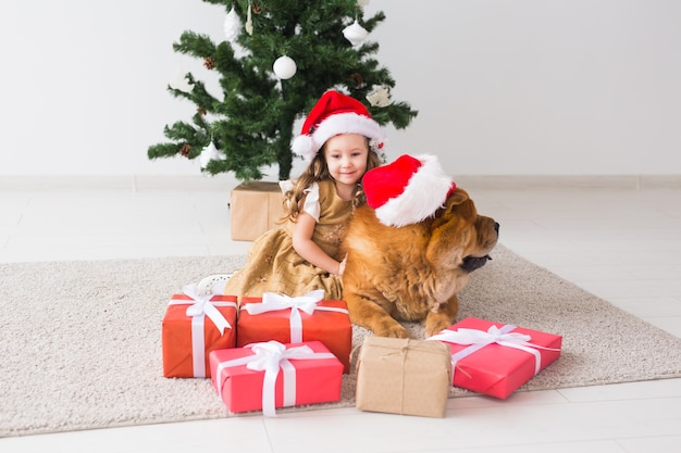 Cute girl with chow dog sitting near the christmas tree