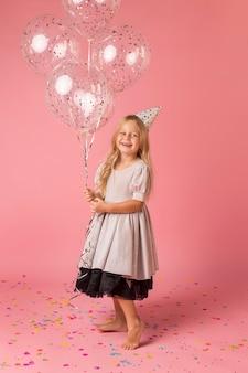 Милая девушка с костюмом и воздушными шарами