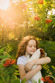 Cute girl with curly hair embraces the puppy