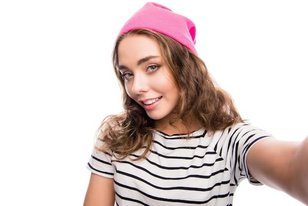 Милая девушка с вьющимися волосами в розовой кепке делает селфи